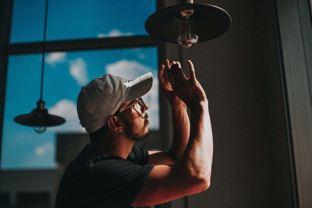 man in black shirt wearing white cap holding clear glass lamp